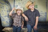 foto of truck farm  - Two Young Boys Wearing Cowboy Hats Leaning Against an Antique Truck in a Rustic Country Setting - JPG