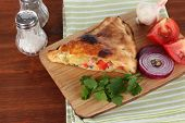 Pizza calzone on wooden board on napkin on wooden table