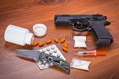 picture of smuggling  - Set of narcotics and handgun on wooden table - JPG