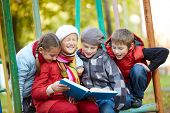 Portrait of happy schoolkids reading book together outdoors