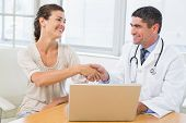 Male doctor and patient shaking hands by laptop at desk in medical office