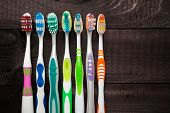 stock photo of toothbrush  - Colorful toothbrushes on black wooden background - JPG