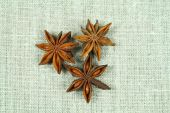 pic of ouzo  - Three whole anise stars on flax background - JPG