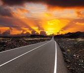 stock photo of canary  - yellow sunset over asphalt road Canary island Lanzarote - JPG