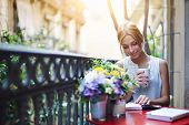Постер, плакат: Pretty young woman reading book while sit at terrace table on her balcony