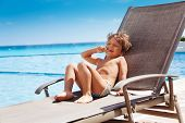 stock photo of sunbather  - Laughing boy laying on sun lounger with finger in his mouth and sunbathing - JPG