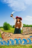 pic of pirate sword  - Girl in costume of pirate with black hat stands on ship made of carton holding sword up in the field - JPG