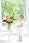 stock photo of girl next door  - Beautiful Toddler Girl Watching Flowers In A Big Vase Next To A Window - JPG