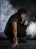 pic of kneeling  - Handsome young man kneeling down in dark hoodie on black background smoke around him - JPG
