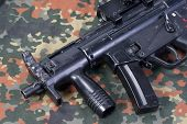 picture of mp5  - modern 9 mm submachine gun on camouflaged background - JPG