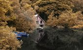 stock photo of derelict  - Derelict old boathouse and rowing boats hidden in forest lake in Autumn - JPG