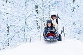 stock photo of snowy hill  - Little Boy Sledding Down A Hill With His Father Helping Him In A Snowy Park - JPG