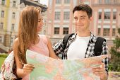 stock photo of lost love  - Close-up portrait of a beautiful couple of tourists holding a map in their hands boy happy looking at the camera and girl looking at boy with love, concept of summer holidays and tourism ** Note: Soft Focus at 100%, best at smaller sizes - JPG