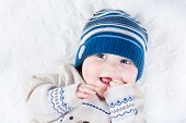 stock photo of teething baby  - Funny Laughing Baby In A Blue Knitted Hat And A Warm Sweater - JPG