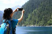 foto of tourist-spot  - woman tourist taking photo with smart phone - JPG