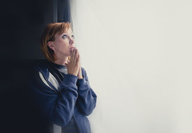 foto of suffering  - young attractive woman suffering depression and stress standing alone in pain praying to god asking for help at window feeling sad and desperate at home with studio backlight - JPG