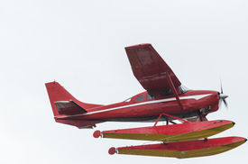 picture of float-plane  - A red float plane flies over head against a washed out sky