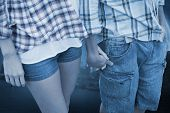 pic of hot pants  - Couple in check shirts and denim holding hands against large moon over river city - JPG