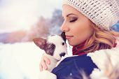 stock photo of snuggle  - Attractive young woman having fun outside in snow with her dog puppy - JPG