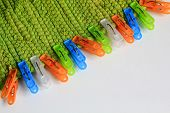 picture of pegging  - colorful plastic clothes pegs on green fabric - JPG
