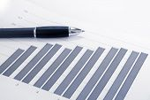 foto of pen  - Financial accounting stock market graphs analysis with pen - JPG