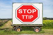 stock photo of european  - rural farm trailer with a big white poster showing a red stop sign and the words Stop TTIP.