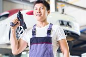 picture of luxury cars  - Asian Chinese car mechanic with tool in front of luxury car in auto workshop - JPG