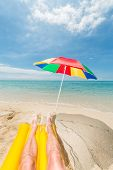 pic of legs air  - male legs on a yellow air mattress relaxing at a beautiful beach with a colorful sunshade - JPG