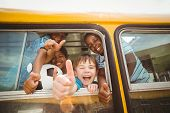 image of pupils  - Cute pupils smiling at camera in the school bus outside the elementary school - JPG