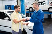 image of key  - Customer shaking hands with mechanic taking keys at the repair garage - JPG