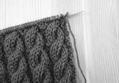 foto of coil  - Coiled rope cable knitting stitch on the needle on a wooden background - monochrome processing