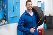 image of garage  - Mechanic smiling at the camera holding tire at the repair garage - JPG
