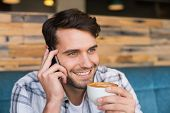 image of cafe  - Young man having cup of coffee at the cafe - JPG