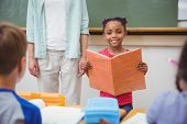 stock photo of pupils  - Cute pupils smiling at camera in classroom at the elementary school - JPG