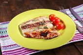 picture of pangasius  - Dish of Pangasius fillet with rosemary and cherry tomatoes in plate on wooden table background - JPG