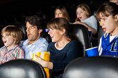 image of watching movie  - Amazed families watching movie in cinema theater - JPG