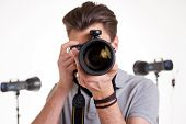 stock photo of shoot out  - Young man in polo shirt shooting you with digital camera while standing in studio with lighting equipment on background - JPG