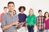stock photo of mans-best-friend  - Cheerful young man holding digital tablet while his friends standing on background ** Note: Visible grain at 100%, best at smaller sizes ** Note: Shallow depth of field - JPG