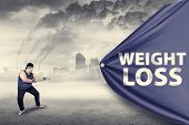 picture of obese man  - Fat man pulling a weight loss banner shot outdoors - JPG