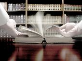 stock photo of law-books  - Hands turning pages in old law book with library in background - JPG