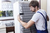 stock photo of handyman  - Handyman trying to move a fridge at house - JPG