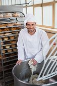 stock photo of mixer  - Smiling baker preparing dough in industrial mixer at the bakery - JPG