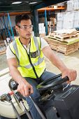 stock photo of forklift driver  - Portrait of driver operating forklift machine in warehouse - JPG