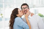 foto of office romance  - Portrait of a woman kissing her colleague in the office - JPG