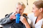 picture of nursing  - Nurse in nursing home giving drink to elderly woman sitting in wheelchair - JPG