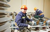 picture of lineman  - Electricians lineman repairman worker at huge power industrial transformer installation work - JPG