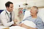 foto of hospital  - Doctor Sitting By Male Patient - JPG