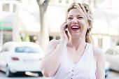 image of laugh out loud  - Curly blond girl talking on her phone and laughing out loud - JPG