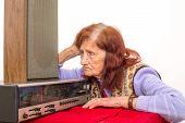stock photo of nod  - Elderly lady listening attentively to the old radio - JPG