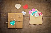 stock photo of revelation  - vintage envelope with colorful hearts and parcel on wooden background - JPG